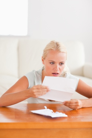 Woman looking at a letter in shock in her living room photo