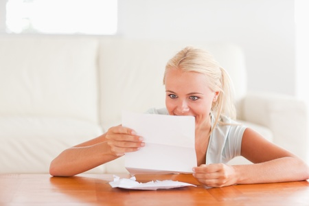 Happy woman reading a letter in her living room photo