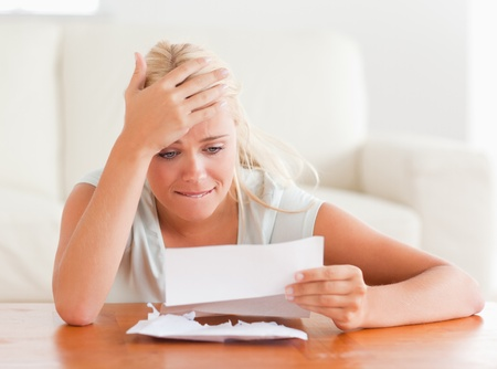 Blond woman in despair holding a letter in her living room photo