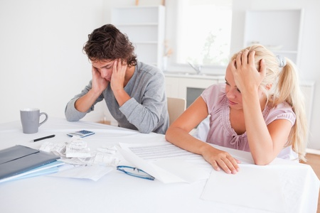 Concerned couple with accountings in their living room photo