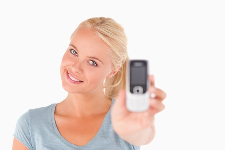 Happy woman showing a mobile in a studio Stock Photo - 11206521