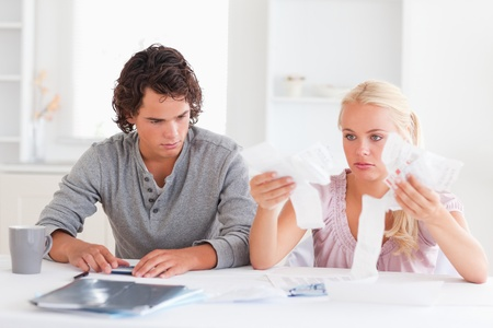 Couple in despaira doing their accounts in a living room photo