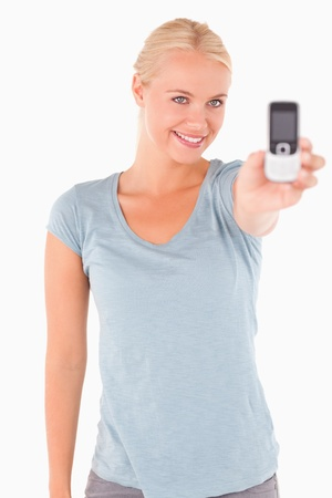 Smiling gorgeous woman showing a phone in a studio Stock Photo - 11225604