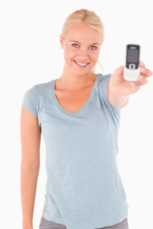 Smiling cute woman showing a phone in a studio Stock Photo - 11201580