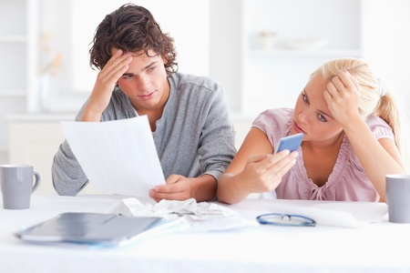 Unhappy couple doing accounts in their living room photo