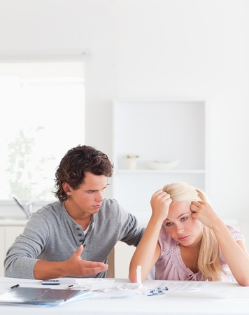 Man trying to comfort his wife in their living room photo