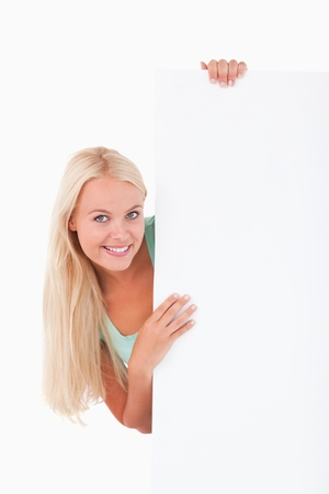 Cute woman standing behind a whiteboard in a studio photo