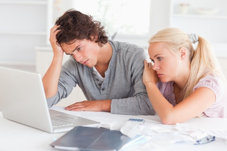Upset couple with bills and a notebook in their living room photo