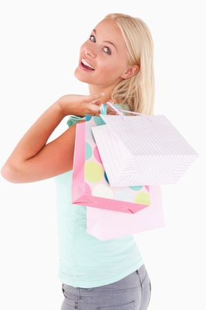 Joyful blond woman with shopping bags in a studio photo