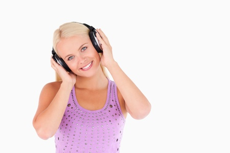 Cute blond woman with earphones in a studio photo