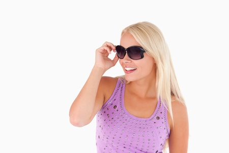 Blond woman with sunglasses in a studio photo