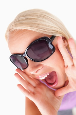 Blond lady with sunglasses in high spirits in a studio photo