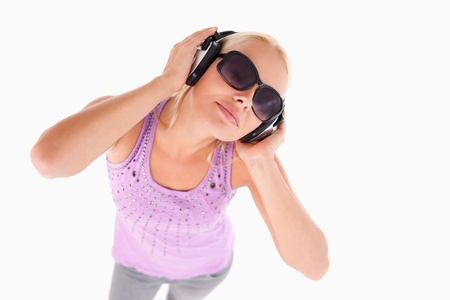 Cheerful lady with sunglasses and earphones in a studio Stock Photo - 11206431