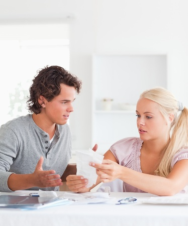 Couple doing their accounts in their living room photo