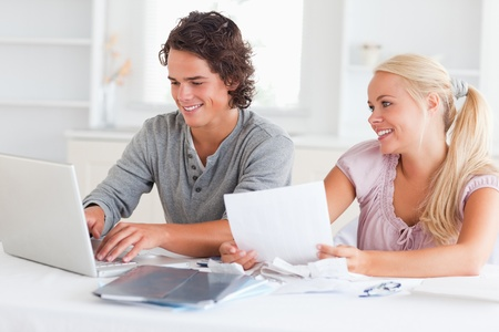 Happy couple accounting in their living room photo