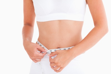 Thin woman measuring her waist in a studio Stock Photo - 11206712