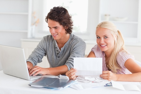 Happy couple doing their accounts in their living room photo