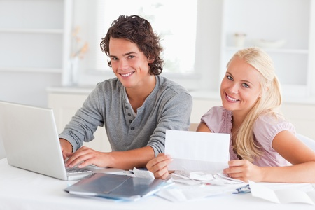 Confident couple accounting in their living room photo