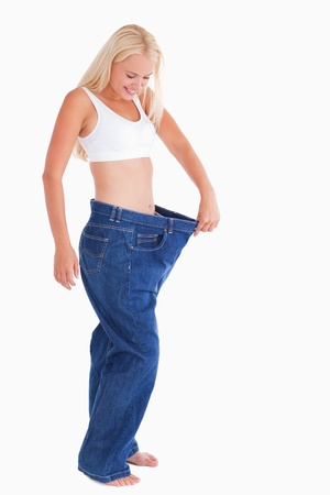 Smiling woman wearing to big jeans in a studio Stock Photo - 11206532
