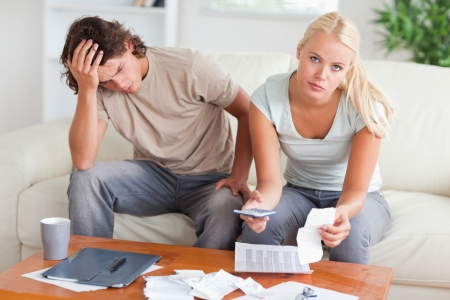 Worried couple calculating their expenses in the living room photo