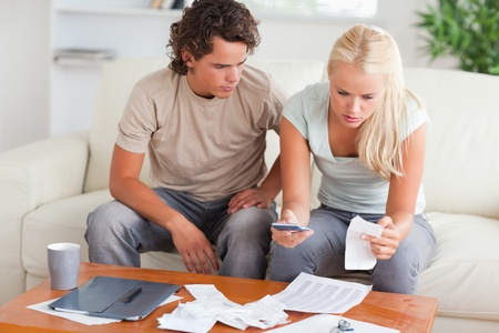 Shocked couple calculating their expenses in the living room photo