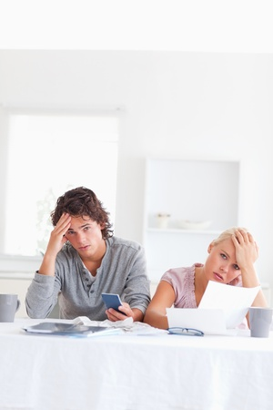 Worn out couple calculating their expenses in the living room photo