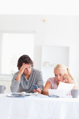 Despaired couple calculating in their living room photo
