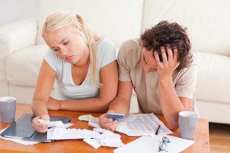 Malheureux dépenses de cotation d'un couple dans le salon Banque d'images