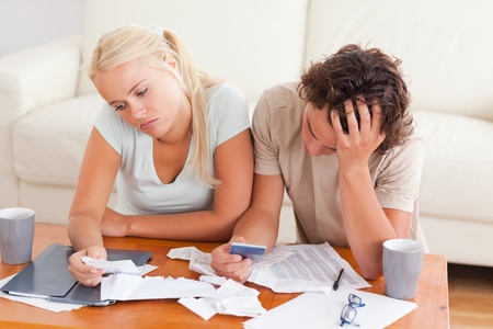 bank crisis: Unhappy couple listing expenses in the living room Stock Photo