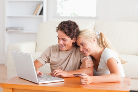 Cute couple with a laptop and a credit card in the living room photo