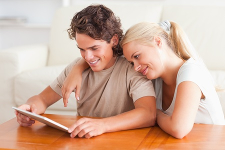 Happy couple with a tablet in the living room photo