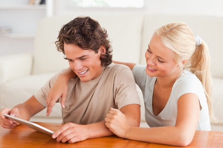Cute couple with a tablet in the living room photo