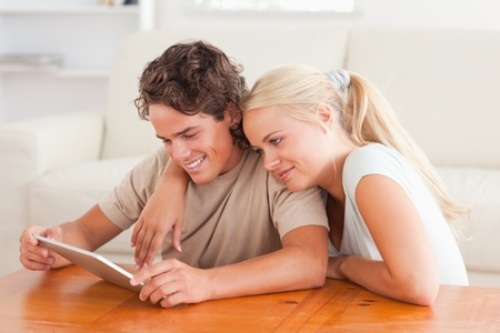 Hugging couple with a tablet in the living room photo
