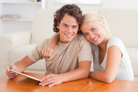 Hugging cute couple with a tablet in the living room photo