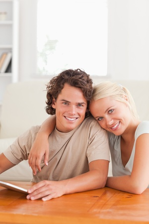 Close up of a Hugging cute couple with a tablet in the living room photo