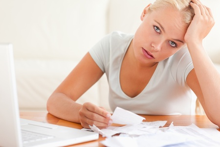 despaired: Despaired woman accounting looking into the camera in the living room Stock Photo