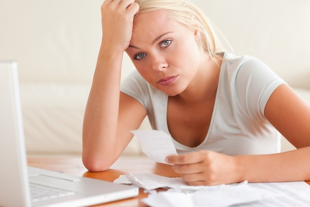 worried woman: Worried woman accounting looking into the camera in the living room