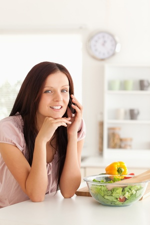 light meal: A woman is telephoning at a table with a salad on it