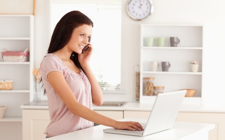 A telephoning woman is typing on her laptop photo