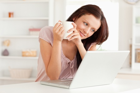 woman drinking coffee: A woman is holding a cup of coffee by laptop