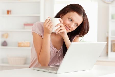 Una mujer sostiene una taza de caf� por la computadora port�til Foto de archivo - 11231047