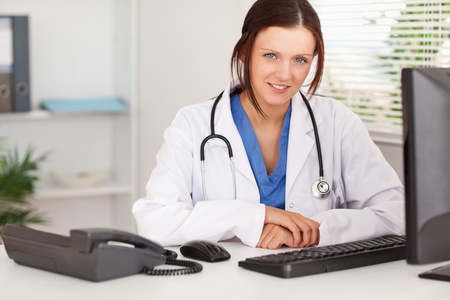 A female doctor is sitting in an office photo