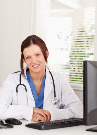 A smiling female doctor is sitting in an office photo