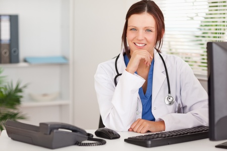 A kind femal doctor is sitting in an office photo