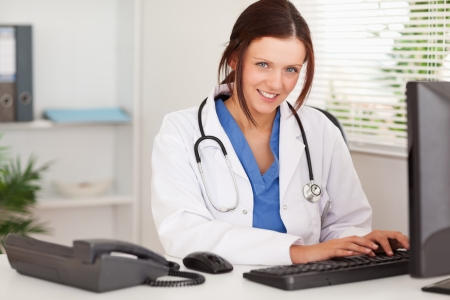 A smiling female doctor is typing on her keyboard  Stock Photo