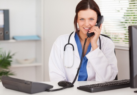 A female doctor is telephoning in an office photo