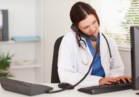 A female doctor is telephoning whilst typing on her keyboard photo