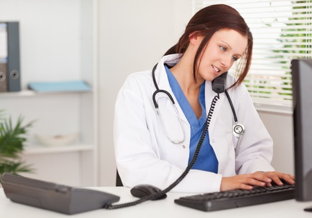 A female doctor is telephoning and typing in her office photo