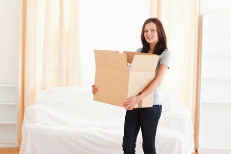 A woman is carrying a cardboard Stock Photo - 11207381