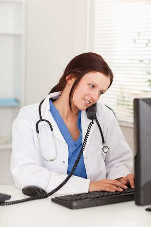 A female doctor is sitting in an office and telephones whilst typing Stock Photo - 11232956